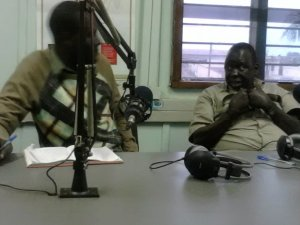 The PRDP coordinator for Gulu district Ocen Peter listens to the LC3 of Odek Sub County Adebe Workorach during a talk show on the PRDP.